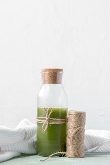 Disposizione con bottiglia di frullato verde