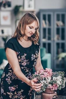 Disposizione della decorazione della maglia dei fiori artificiali a casa, lavoro del fiorista della giovane donna che fa l'organizzazione del fiore artificiale fai da te