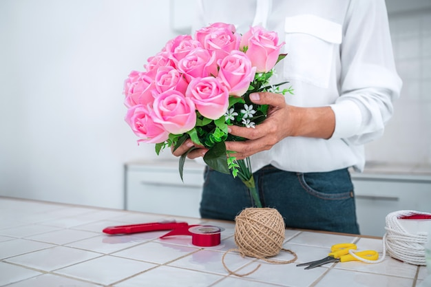 Disposizione di fiori artificiali, lavoro di fiorista della giovane donna che organizza fiori artificiali fai da te