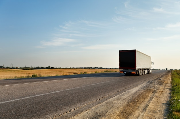 Camion in arrivo sulla strada in un paesaggio rurale al tramonto Foto Premium