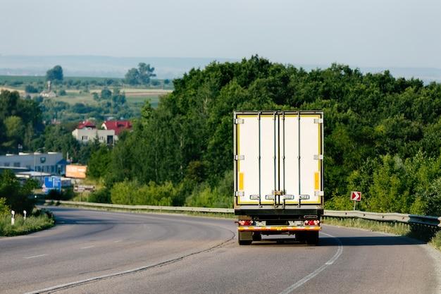 Camion in arrivo sulla strada in un paesaggio rurale al tramonto