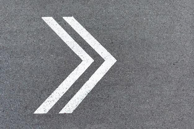 Il puntatore a freccia è disegnato con vernice bianca sulla strada. cartello svolta a destra su asfalto, senso di marcia