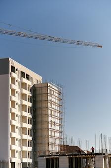 Freccia di una gru a torre sulla costruzione di un edificio a più piani