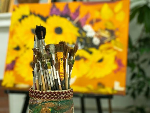 Pennelli artistici in un portabicchieri su sfondo giallo colorato.