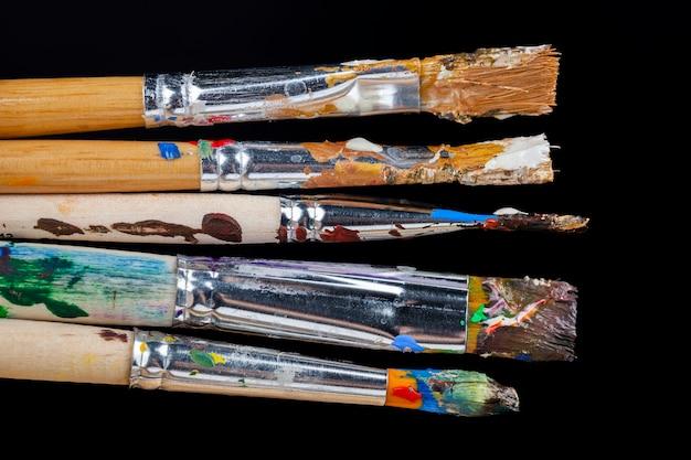 Pennelli artistici imbrattati di vernici di diversi colori dopo aver disegnato le immagini