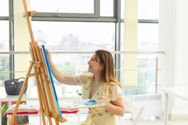 Classe d'arte, disegno e concetto di creatività - studentessa seduta davanti al cavalletto con tavolozza e pennello