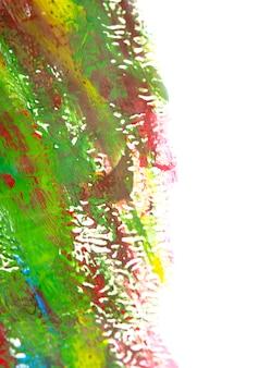 Tela creativa artistica con linee disegnate di vernice blu, verde gialla, rossa. disegno dipinto con colori a guazzo di diversi colori su superficie bianca. primo piano del movimento della pittura. pennellate multicolori