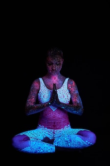 Cosmo ragazza d'arte alla luce ultravioletta. la donna fa yoga, riscaldamento del corpo. l'intero corpo è ricoperto di goccioline colorate. yoga astrale. rumore, fuori fuoco