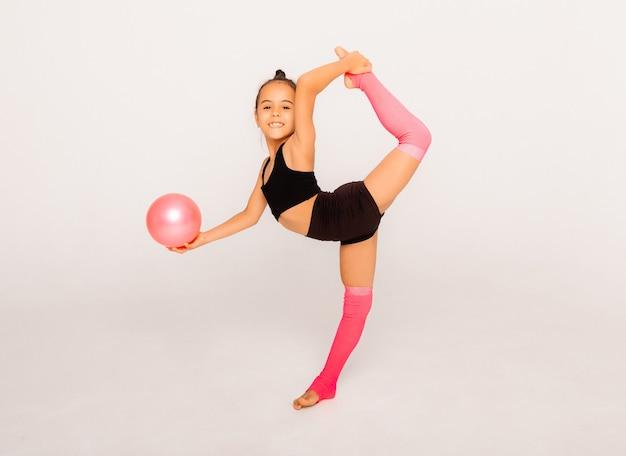 Ginnastica artistica. la bambina flessibile si esibisce con una palla su uno sfondo bianco.