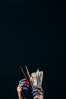 Stile di vita per il tempo libero hobby arte. mani di artista creativo. spalmato di vernice che tiene i pennelli. progetto in corso. selezione degli strumenti.