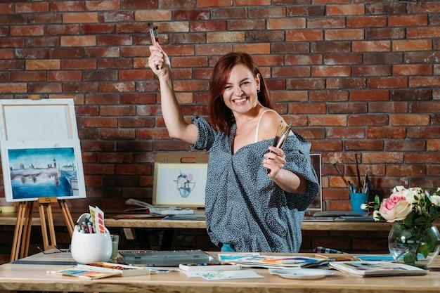 Hobby d'arte. atmosfera dell'area di lavoro dello studio. femmina entusiasta della testarossa che posa con i pennelli e il cavalletto