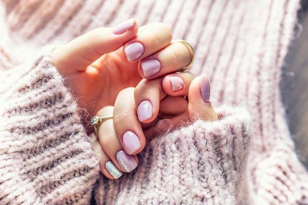 Manicure per unghie artistiche per la sposa in maglione viola. unghie in gel di colore rosa tenue.