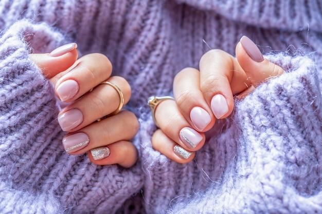 Manicure per unghie artistiche per la sposa in maglione viola. unghie in gel di colore viola tenue.