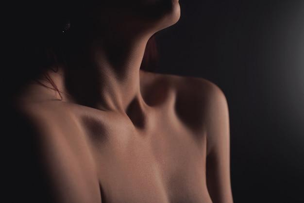 Arte nuda, corpo nudo perfetto, giovane donna sexy su una parete scura in bagno, fotografia in bianco e nero,