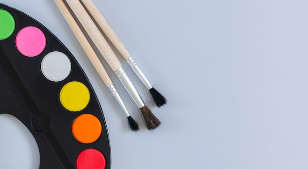 Tavolozza di arte con vernice e pennelli vista dall'alto sulla superficie grigia, banner con spazio di copia