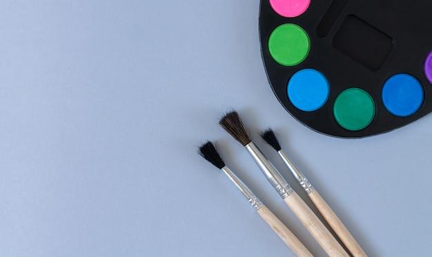 Tavolozza di arte con vernice e pennelli vista dall'alto sulla superficie grigia con spazio di copia