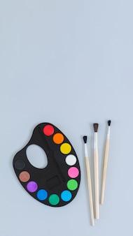 Tavolozza di arte con vernice e pennelli vista dall'alto sul muro grigio