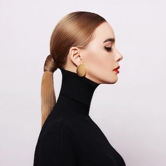 Ritratto d'arte di una donna bella ed elegante con un dolcevita nero e gioielli in oro