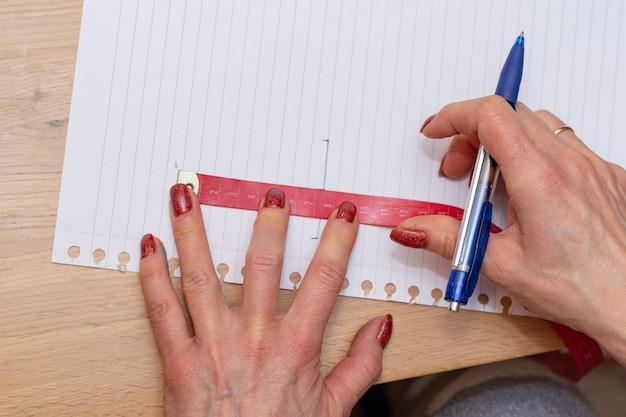 La preparazione del progetto artistico mani che tengono nastro e penna per misurare e ricalcare su carta.