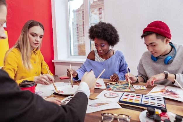 Studenti d'arte. due studenti creativi di talento e due studentesse d'arte dipingono insieme in classe