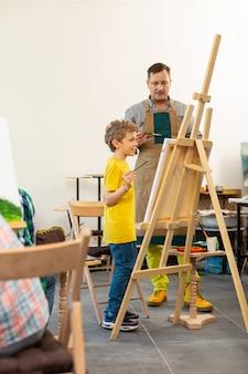 Insegnante di arte che aiuta il suo giovane allievo creativo vicino al cavalletto di disegno
