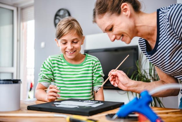 Insegnante di arte che aiuta uno studente a dipingere