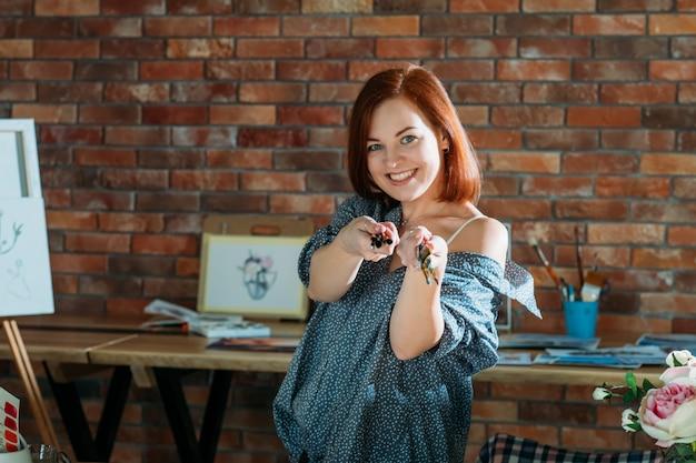 Terapia artistica. atmosfera da studio antistress. sorridente donna rossa che si estende pennelli.
