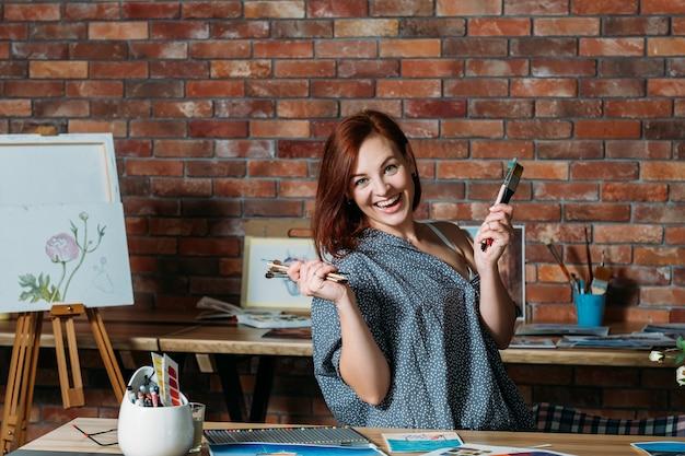 Terapia artistica. atmosfera da studio antistress. donna sorridente della testarossa che posa con i pennelli.