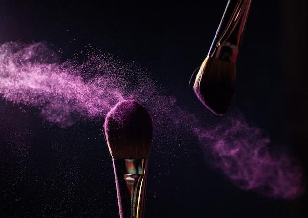 Arte del viso. foto del primo piano di due pennelli neri professionali per il trucco con polvere viola isolato su priorità bassa nera con il posto della copia.