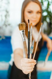 L'arte, il lavoro dell'artista. la giovane bella ragazza artista dipinge un'immagine. bottega dell'artista. il processo di creatività. disegnare e dipingere. inventario dell'artista. avvicinamento.