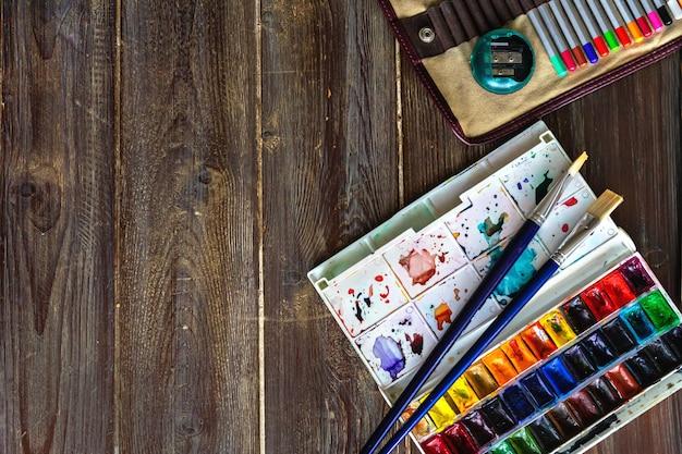 Luogo di lavoro d'arte, matite colorate, pennelli e colori ad acquerello