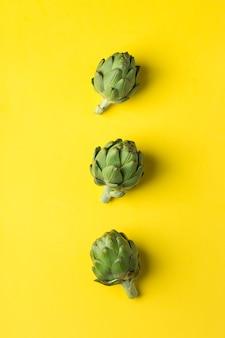 Carciofo su sfondo giallo mangia sano concept
