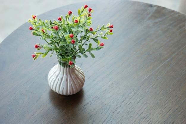 Fiore artificiale in una pentola su un tavolo di legno
