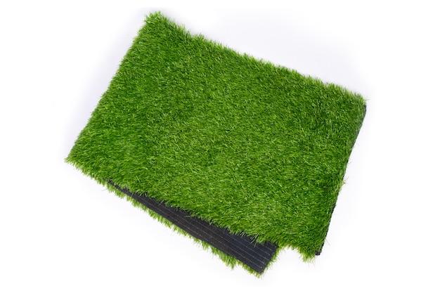 Erba artificiale per campi sportivi, erba di plastica verde su sfondo bianco.