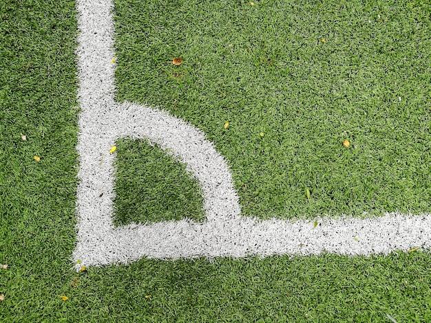 Campo di erba artificiale di calcio all'angolo, fondo di sport