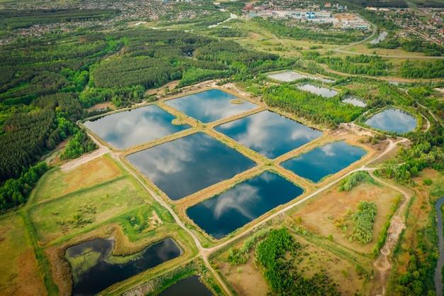 Stagni artificiali di stoccaggio per il trattamento dell'acqua della città. natura del riflesso del cielo nell'acqua. vista dall'alto