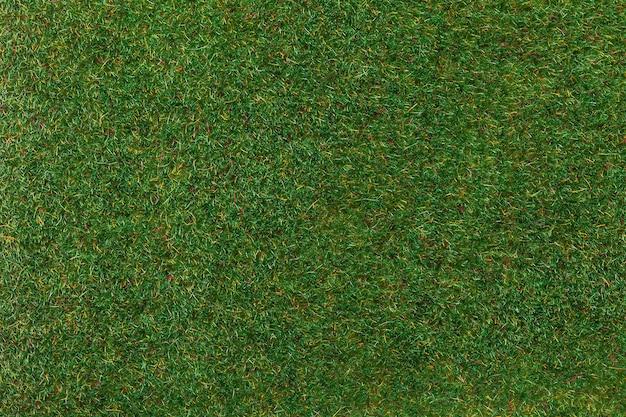 Tappeto erboso artificiale per campo sportivo e decorare il cortile, sfondo macro. texture di tappeto di erba verde, sfondo.