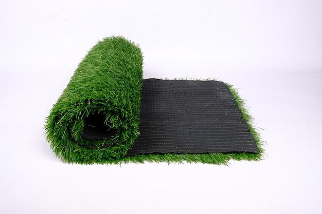 Tappeto erboso artificiale per sport e campi da gioco, rotolo di prato isolato sul muro bianco.