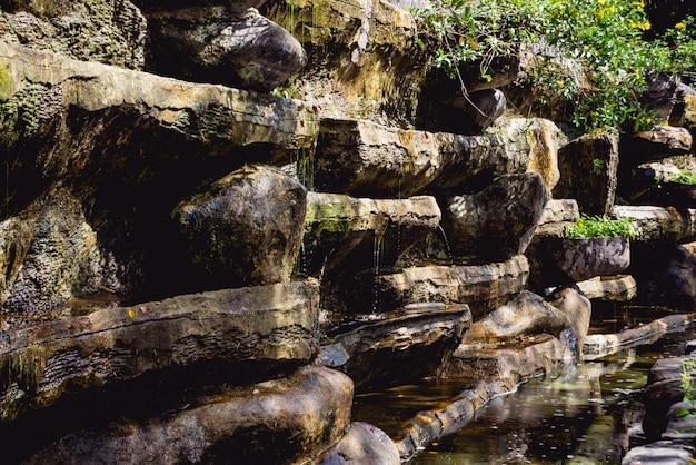 Cascata artificiale al giardino botanico. pietre e acqua