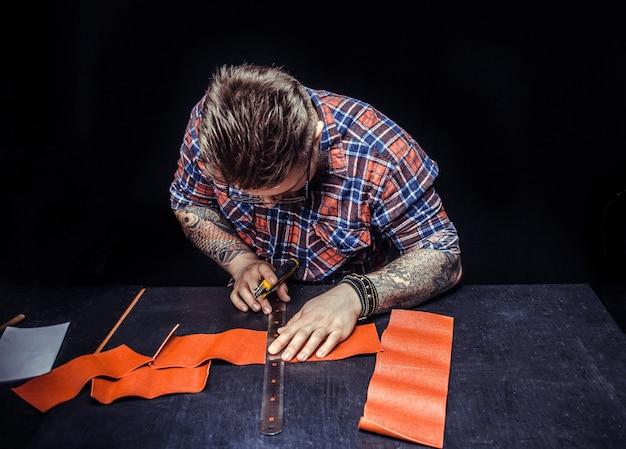 Artigiano taglio pezzo di cuoio arancione con coltello