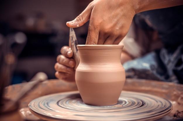 La ragazza artigiana mostra il processo di realizzazione di piatti in ceramica utilizzando la vecchia tecnologia.