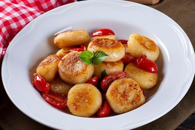 Gnocchi artigianali ripieni di formaggio, con pomodorini, aglio, olio d'oliva e basilico