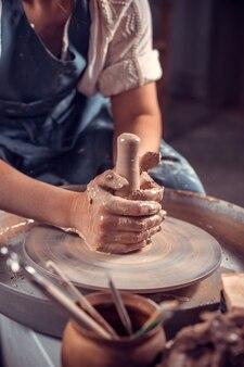 Artigiano al suo volante per creare un nuovo capolavoro. fare piatti in ceramica. avvicinamento.