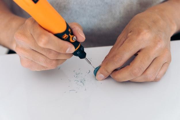 Persona artigiana che utilizza strumenti e attrezzature per realizzare orecchini fatti a mano.