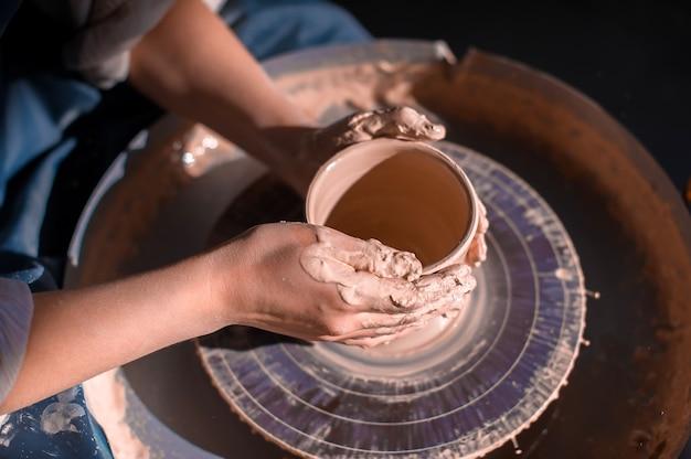 Scultore artigiano lavora con l'argilla su una ruota da vasaio e al tavolo con gli strumenti