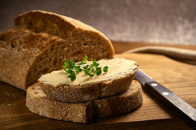 Pane tostato artigianale a fette con burro e broccoli microgreen su tagliere di legno con coltello