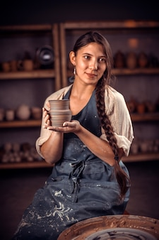 Donna artigiana mostra il prodotto finito di argilla in officina. restauro di tradizioni ceramiche dimenticate.