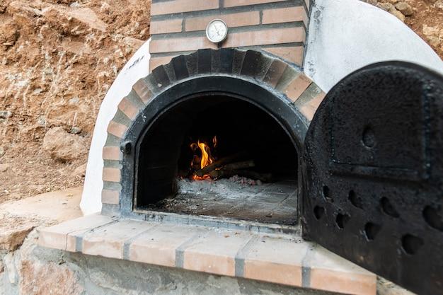 Forno a legna artigianale costruito all'esterno con la porta aperta e fuoco all'interno