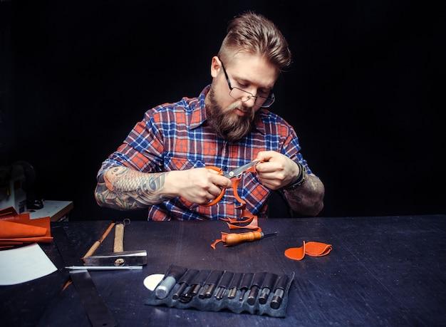 L'artigiano che lavora con la pelle elabora un pezzo in lavorazione dalla pelle nel suo luogo di lavoro