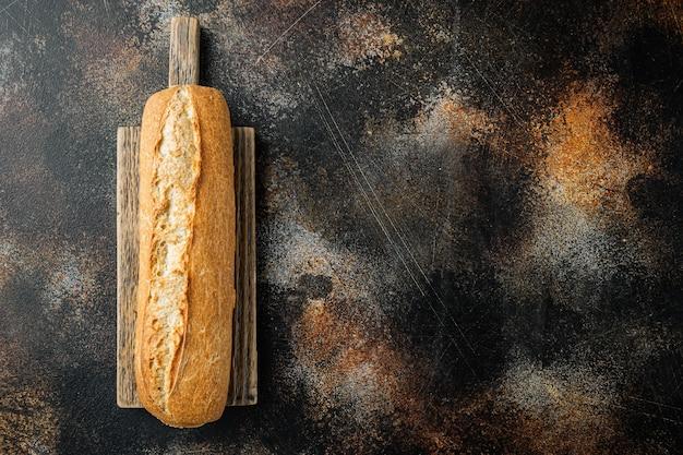 Pane baguette artigianale, su vecchio sfondo rustico scuro, vista dall'alto piatta con spazio per la copia per il testo